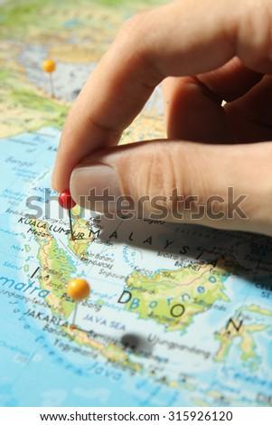 Fingers placing pin on Kuala Lumpur city on map - stock photo