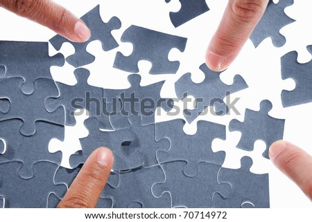 Fingers trying to solve the scattered puzzle - stock photo