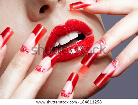 Fingers with red french acrylic nails manicure and paiting - stock photo