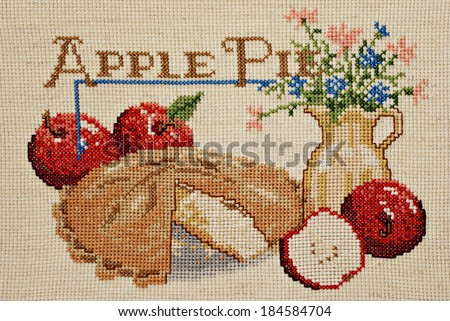 Finished cross stitch design of apple pie still life (worked on homespun aida cloth) - stock photo