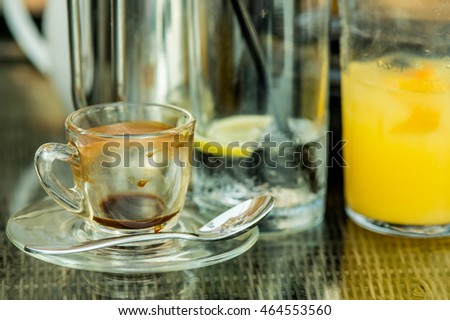 Finished Espresso Coffee and Glasses of Iced Water and Orange Juice on a Table After a Meal