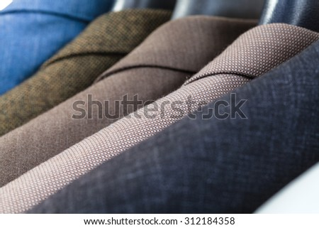 finished jackets on hangers in tailoring atelier close up - stock photo