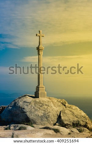 Finisterrae, Spain - July 29, 2011: Cross of the Coast of Death illuminated at the front by a warm sunset.