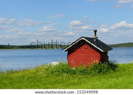 Finnish sauna on shore of blue lake, Northern Finland, Lapland - stock photo