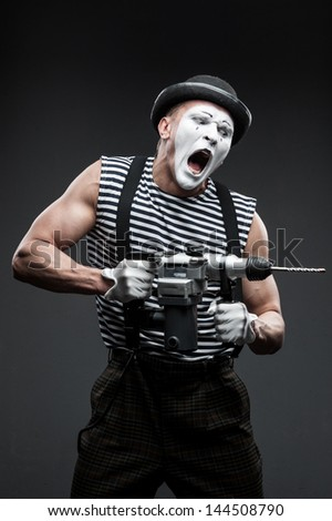 finny aggressive mime holding puncher - stock photo