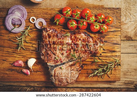Fiorentina steak grilled with spices and vegetables on a rustic wooden table - stock photo