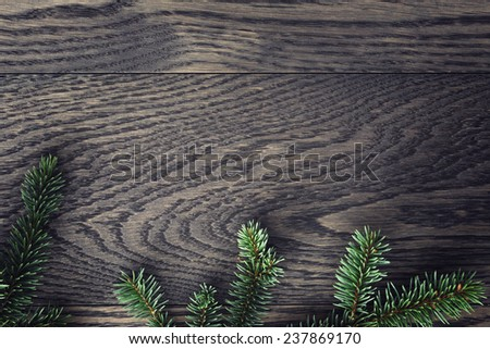 fir branch on stained oak table from above, vintage toned - stock photo