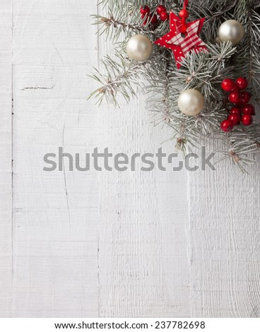 Fir branch with Christmas decorations on the white wooden plank. Focus on Christmas decorations - stock photo