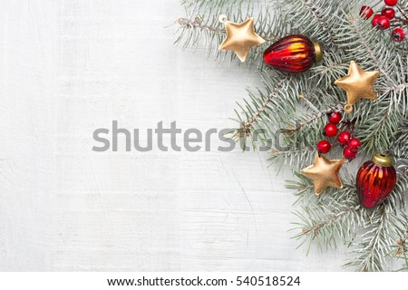 Fir branch with Christmas decorations on white rustic wooden background with copy space for text.