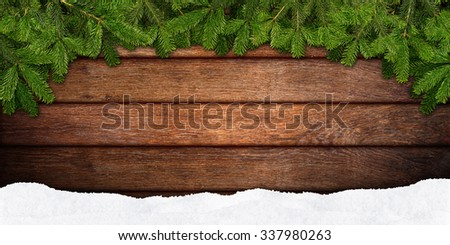 fir branches and snow on wooden background