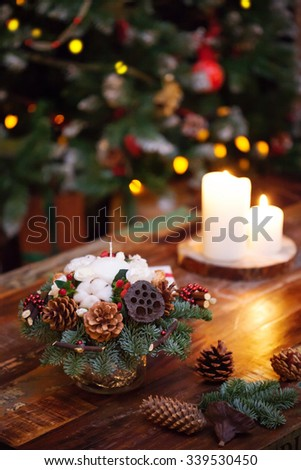 Fir branches decorated for the new year on dark wooden background. Christmas tree and candles, festive mood - stock photo