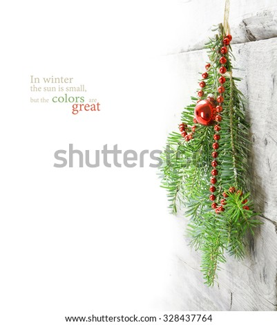 fir branches with Christmas baubles hanging as a winter decoration on a light wooden wall, background with copy space faded to white, sample text In winter the sun is small, but the colors are great - stock photo