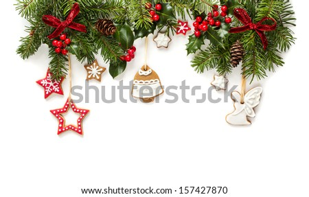 Fir tree and holly branches decoration with gingerbread for Christmas. Isolated on white background - stock photo