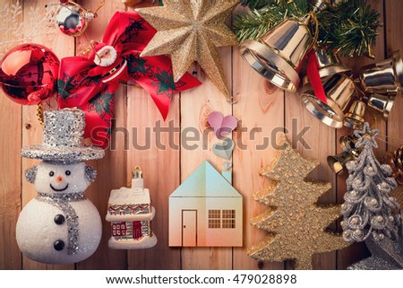 Fir tree branch with christmas lights, gift box and candy canes with house paper cut flat style on wooden background with copy space
