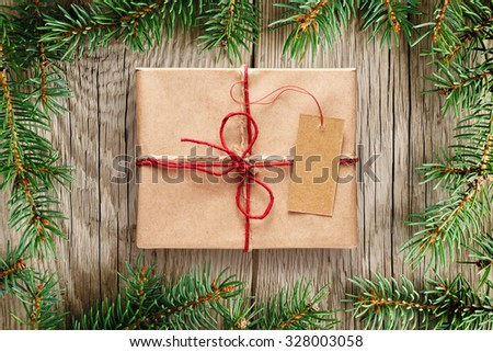 Fir tree branches and gift box with tag on wooden background - stock photo