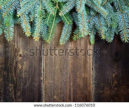 fir tree branches over old wooden background - stock photo