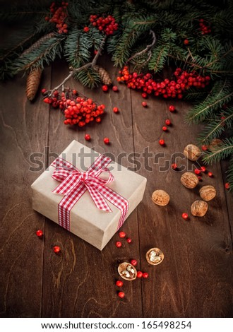 Fir tree  branches, rowan berries, Christmas gift on a wooden background