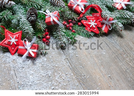 Fir tree branches with christmas gift boxes on old wooden board - stock photo