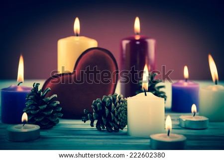 fir-tree cones and candles on a wooden background - stock photo