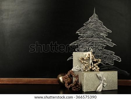 Fir tree drawing on blackboard and beautiful gifts. Xmas background - stock photo