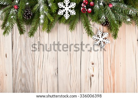 Fir tree with christmas decorations on wooden background