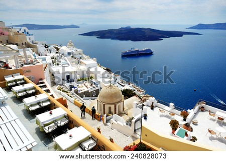 FIRA, GREECE - MAY 17: The view on Fira town and tourists enjoying their vacation on May 17, 2014 in Fira, Greece. Up to 16 mln tourists is expected to visit Greece in year 2014.