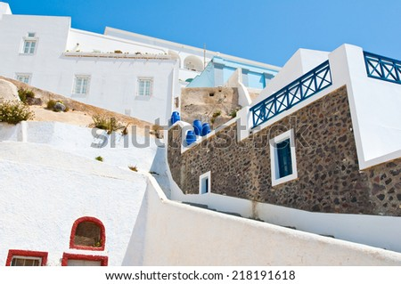 Fira street with whitewashed and blue houses on the island of Thira (Santorini), Greece. - stock photo
