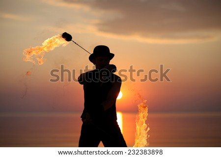 Fire act on the beach - stock photo