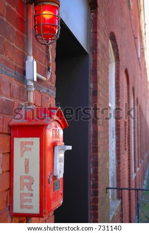 Fire alarm call box on factory wall - stock photo