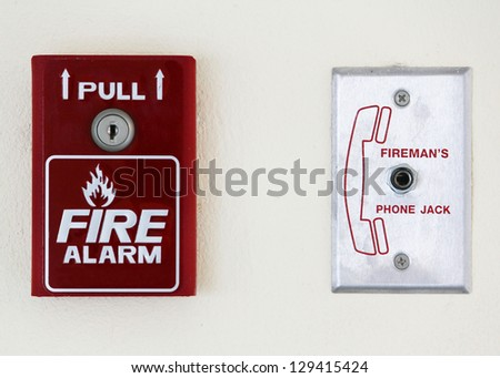 Fire alarm switch over a sign showing a fire and text fire alarm on a wall