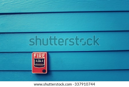 Fire alarm with blue painted wood background - stock photo