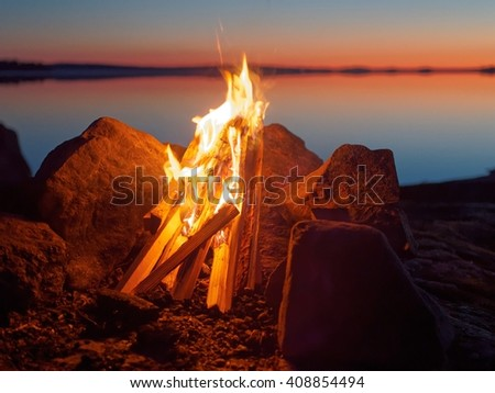 Fire and flames of atmospheric campfire on the beach at night. Still water of the lake on the background with warm colors of sunset. Very shallow dept of field.      - stock photo