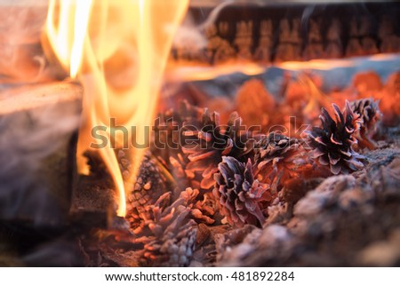 Fire and smoke in the fireplace, burning and smoldering lumps of coal. Christmas symbol.