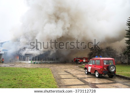 Fire and strong smoke covered building - stock photo