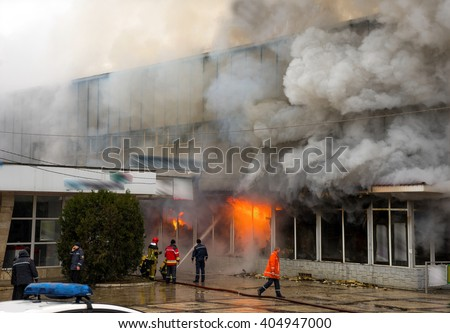 Fire and strong smoke covered building. Dangerous situation - stock photo