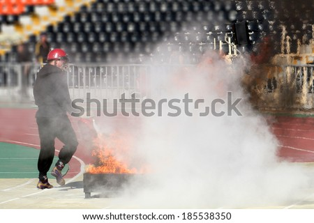 Fire Applied Sport firefighter puts out a fire extinguisher - stock photo