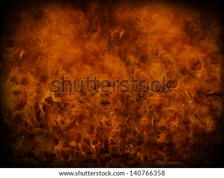 Fire background with small skulls hiding in the flames. Great for music and heavy metal styles. - stock photo