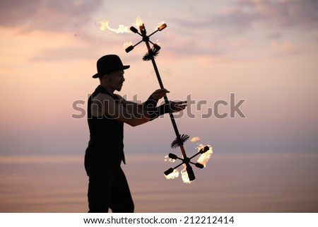 Fire baton twirling by a showman on sunset background - stock photo