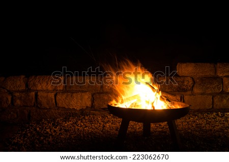 fire bowl with stack of wood - stock photo