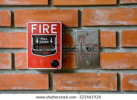 fire break glass alarm switch on brick wall background - stock photo