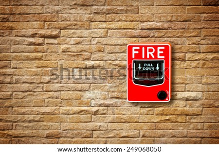 fire break glass alarm switch on the stone wall - stock photo