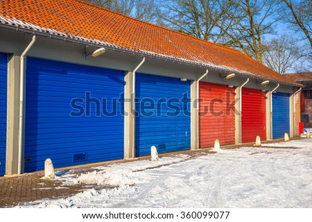 Fire Brigade and Frost roads service Garage Doors in blue and red next to each other on a Snowy Winter Day