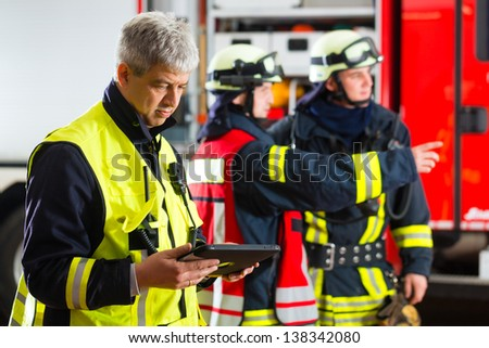Fire brigade - Squad leader, he used the Tablet Computer to plan the deployment and looking at the viewer - stock photo