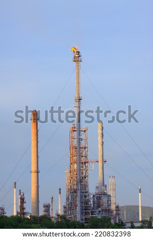 fire burning over oil refinery chimney against blue sky