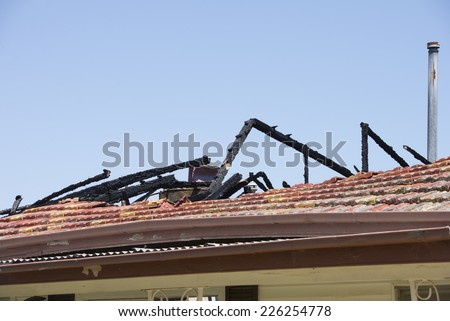 Fire damaged roof on house building, with charred black timber beams, broken tiles and chimney, blue sky as background and copy space.