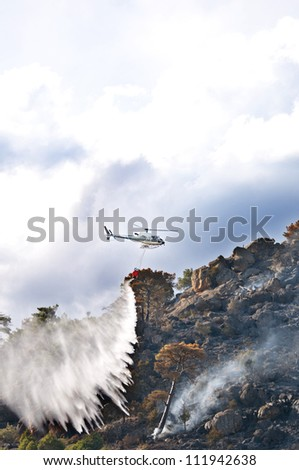 Fire Department helicopter  dropping water from a  water bucket to fight a forest fire near Robledo, Spain. - stock photo
