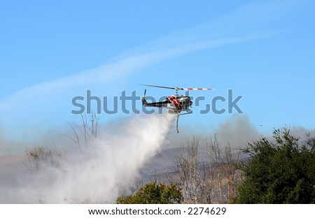 fire department helicopter in action dropping water