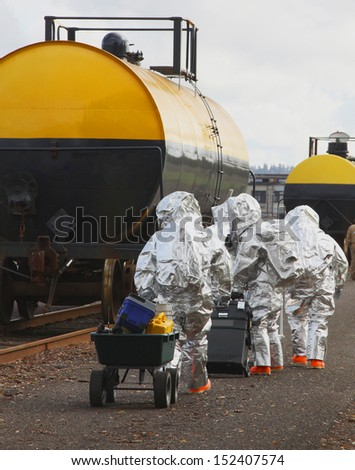 Fire departments and emergency response teams conduct disaster preparedness drills. The HAZMAT team members are suited up with protective suits as they travel to this mock railroad disaster. - stock photo