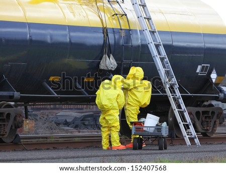 Fire departments and emergency response teams will conduct disaster preparedness drills. These HAZMAT team members are passing tools up to the others on the rail tanker to repair the chemical leak. - stock photo