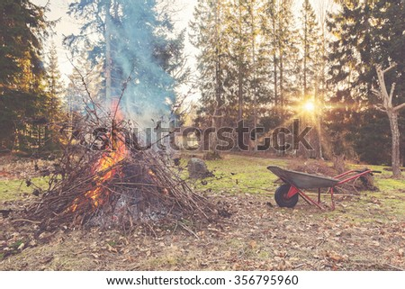 Fire during cleanup of garden with sun setting and an old wheelbarrow. Filter